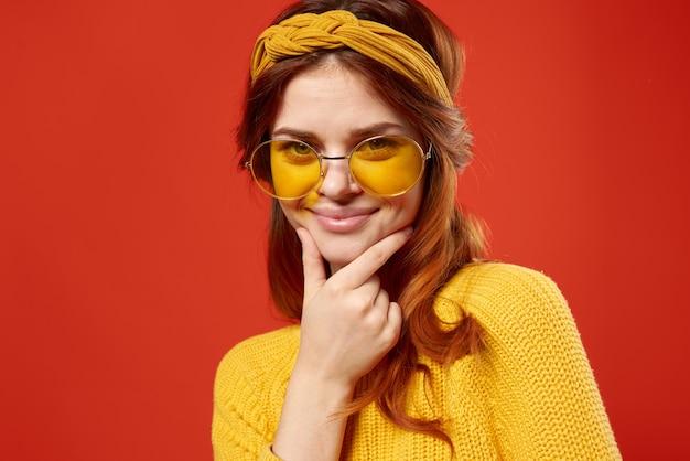 Mujer emocional con gafas suéter amarillo ropa casual hippie pared roja.