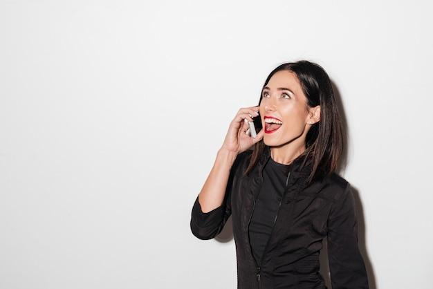 Mujer emocional con labios rojos hablando por teléfono móvil.
