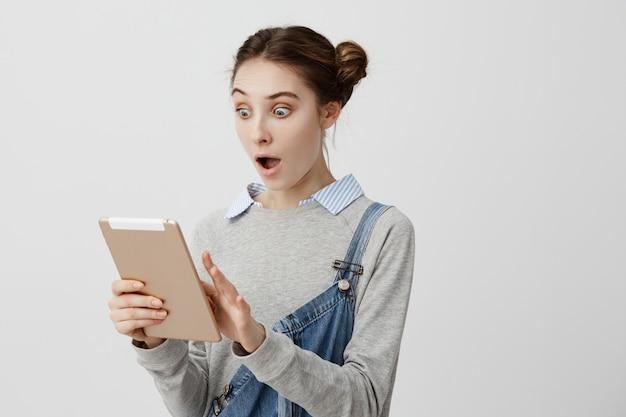 Mujer emocional leyendo información inesperada en gadget con la boca abierta y ojos saltones. chica de pelo oscuro con apariencia caucásica mirando en la computadora portátil diciendo wow amando sus características. copia espacio