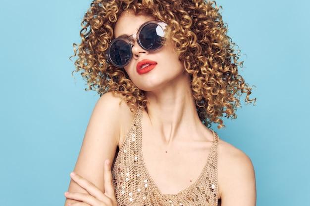 Mujer emocional pelo rizado labios rojos gafas de sol maquillaje brillante azul pared aislada