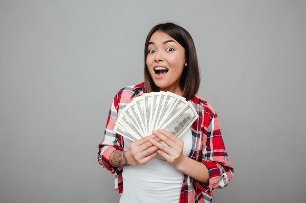 Mujer emocional que sostiene el dinero sobre la pared gris.