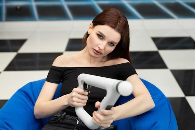 Una mujer emocional se sienta en una silla y juega a playstation vr con un mando aim.