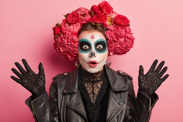 Mujer emocional sorprendida con maquillaje aplicado en forma de calavera, sonrisa pintada, levanta las manos, usa guantes de encaje negro, chaqueta de cuero