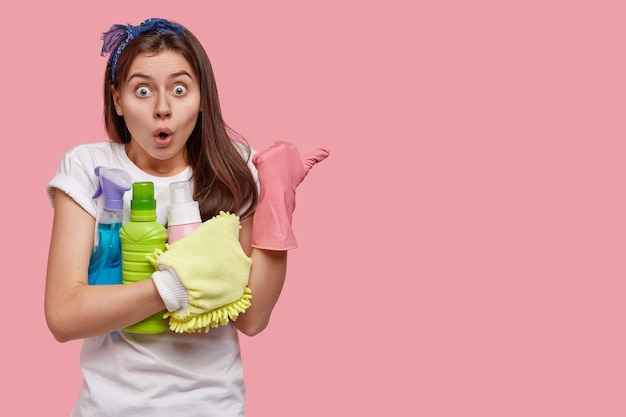 Mujer emotiva asustada con expresión de sorpresa, usa diadema, lleva detergentes químicos, indica a un lado