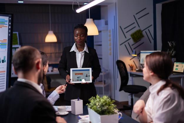 Mujer emprendedora adicta al trabajo concentrada con piel oscura que explica la estrategia de gestión