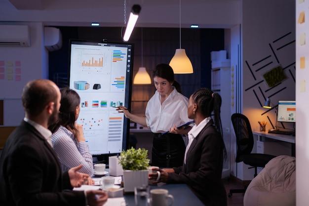 Mujer emprendedora adicta al trabajo discutiendo estadísticas de gestión exceso de trabajo en la sala de reuniones de la oficina a altas horas de la noche