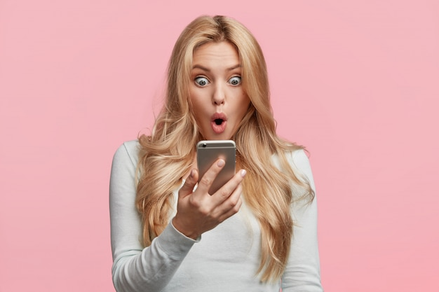 Mujer emprendedora o empresaria decepcionada con las noticias de su colega, lee el mensaje en el teléfono inteligente, sorprendida de recibir la responsabilidad de preparar un proyecto difícil para la reunión de mañana