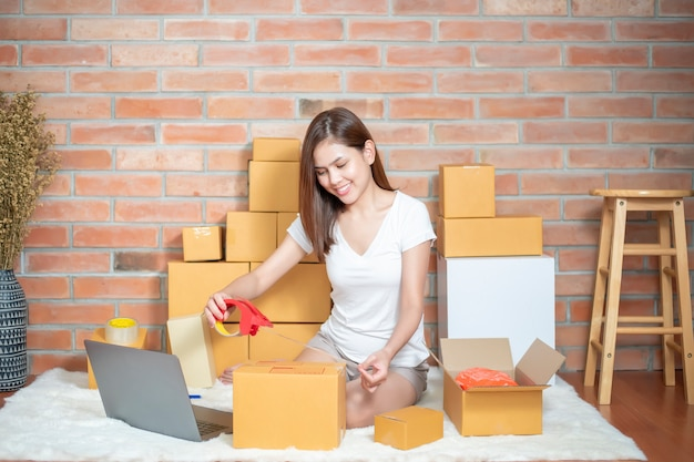 La mujer emprendedora propietaria de un negocio sme está revisando el pedido con teléfono, computadora portátil y caja de embalaje para enviar a su cliente