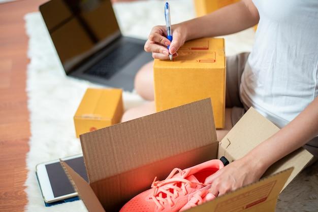 La mujer emprendedora propietaria del negocio sme está revisando el pedido con un teléfono inteligente, una computadora portátil y una caja de embalaje para enviar a su cliente