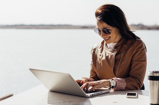Mujer emprendedora trabajando con una laptop en la terraza de una casa.