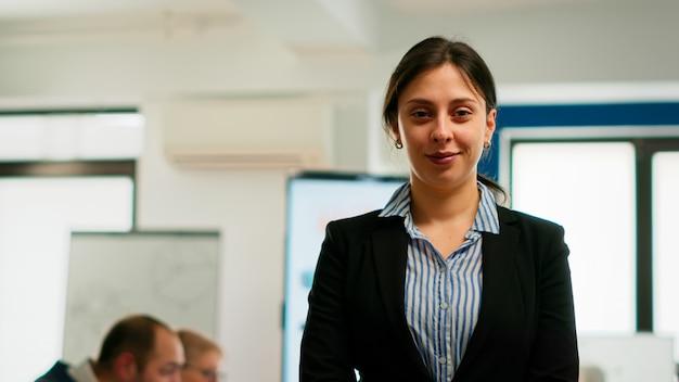 Mujer empresaria sonriendo a la cámara de pie en la sala de conferencias, preparándose para reunirse con socios. gerente de proyecto que trabaja en la puesta en marcha de un negocio financiero profesional listo para la lluvia de ideas