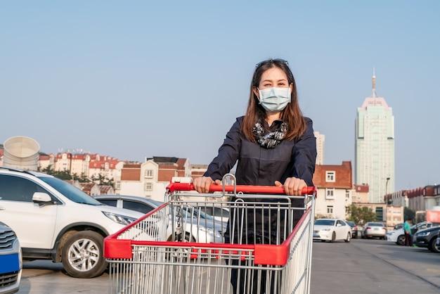 Mujer empujando carrito de compras en el estacionamiento