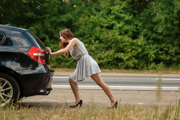 Mujer empujando el coche roto en la carretera, avería