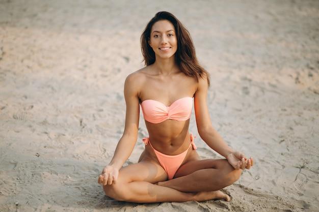 Mujer en bikini practicando yoga en la playa