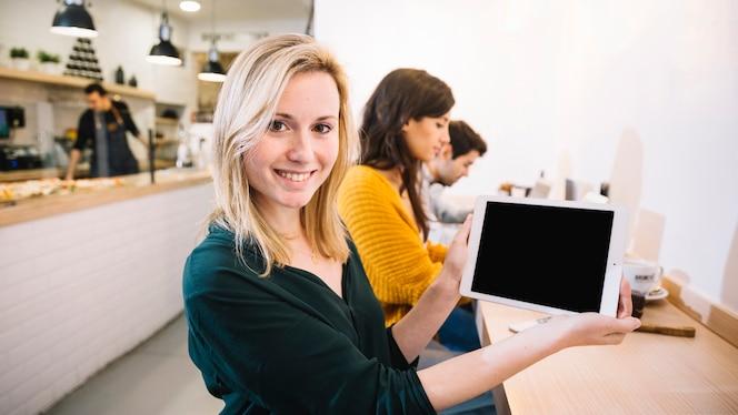 Mujer en café que muestra la pantalla de la tableta