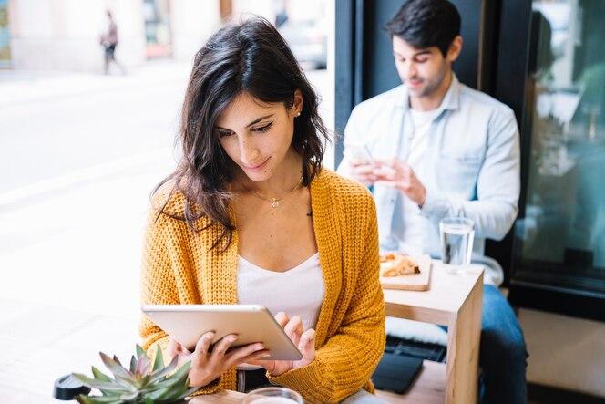 Mujer en café trabajando en tableta