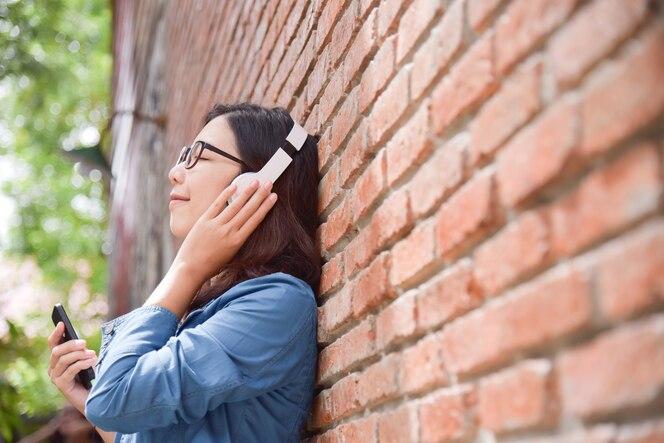 Mujer en camisa azul escuchando la música con auriculares.