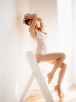 Mujer en lencería blanca seductora se sienta en la escalera
