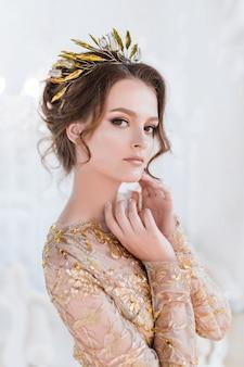 Mujer en oro tarde gawn y corona posa en la habitación blanca de lujo