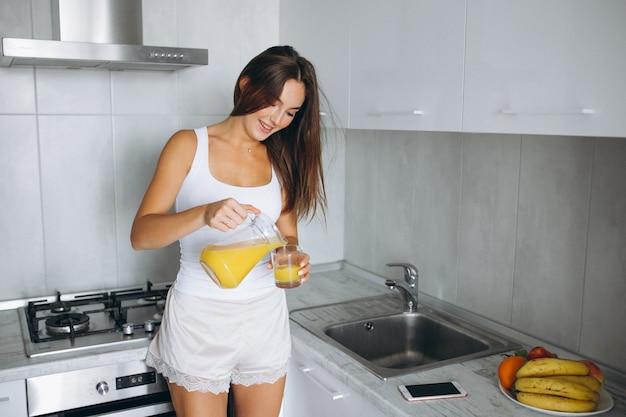 Mujer en su cocina bebiendo jugo