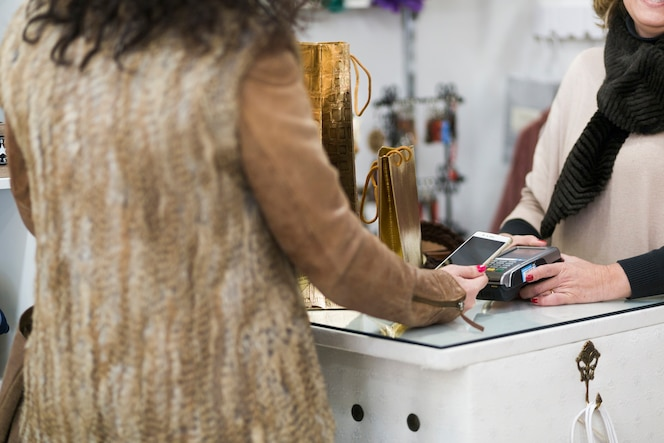 Mujer en tienda pagando con teléfono inteligente