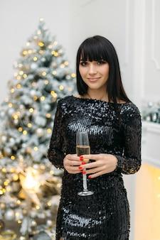 Mujer en vestido negro brillante se encuentra delante de un árbol de navidad