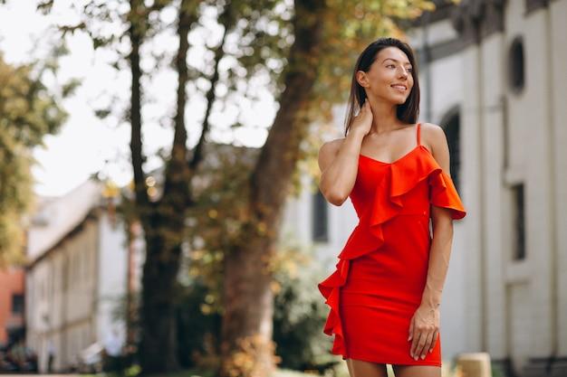 Mujer en vestido rojo afuera en la ciudad