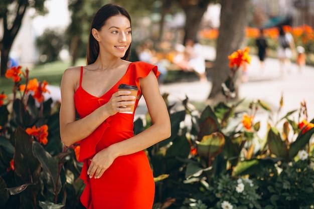 Mujer en vestido rojo tomando café para salir al parque