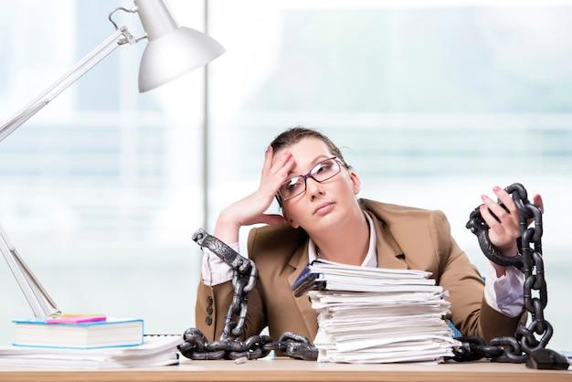 Mujer encadenada a su escritorio de trabajo.