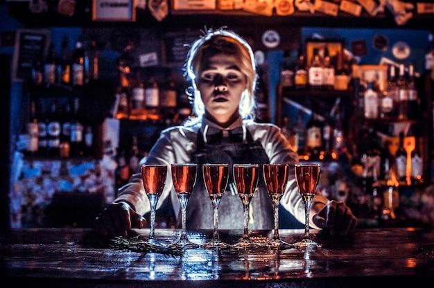 Mujer encantadora camarera da los toques finales a una bebida en la barra del bar