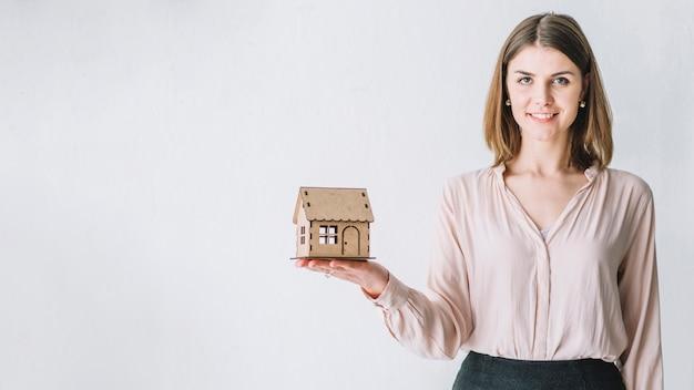 Mujer encantadora con casa de juguete