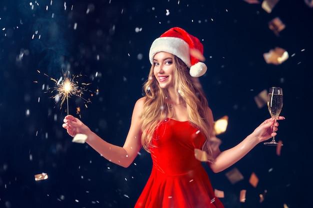 Mujer encantadora celebrando la navidad en vestido rojo