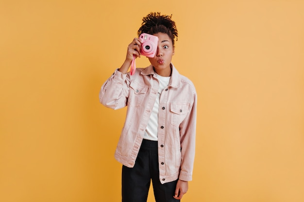 Mujer encantadora en chaqueta tomando fotos