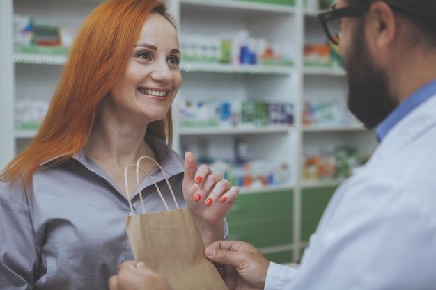 Mujer encantadora compra medicamento en farmacia