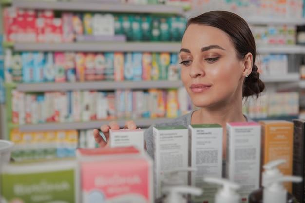Mujer encantadora de compras en la farmacia