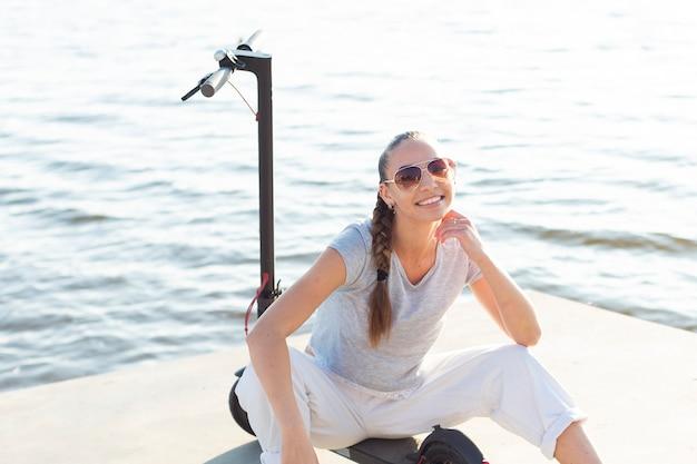 Mujer encantadora con gafas de sol posando en scooter