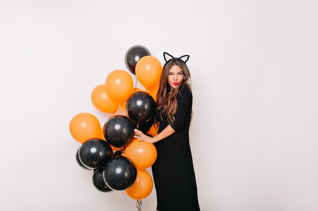 Mujer encantadora con globos de halloween posando con placer en la pared blanca