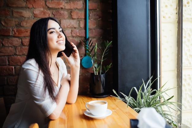 Mujer encantadora joven llamando con teléfono celular mientras está sentado solo en la cafetería.