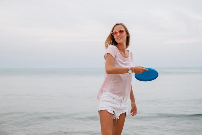 Mujer encantadora joven que juega el disco volador cerca del mar, sosteniendo el disco del disco volador.