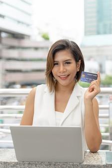 Mujer encantadora joven que muestra la tarjeta de crédito para el pago de compras en línea con la computadora portátil