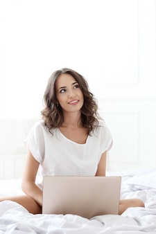 Mujer encantadora con laptop en la cama