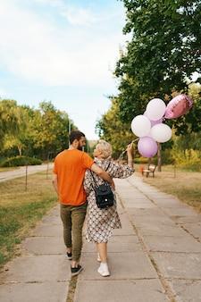 Mujer encantadora con mochila y hombre casual caminando feliz con globos rosas en el parque. libertad y concepto de mujer sana.