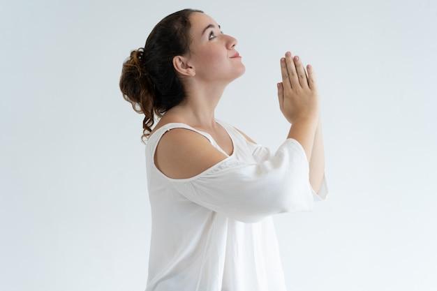 Mujer encantadora positiva que lleva a cabo las manos juntas y que ruega