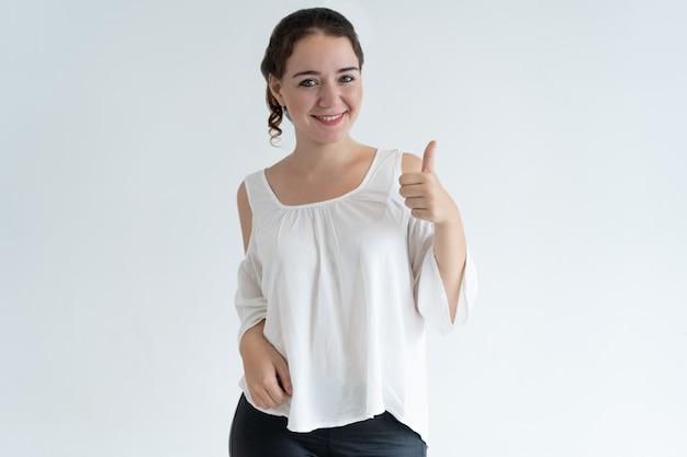Mujer encantadora positiva que muestra el pulgar hacia arriba
