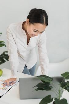 Mujer encantadora que controla la computadora portátil