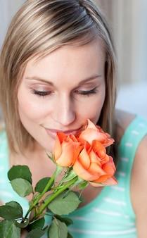 Mujer encantadora que huele rosas