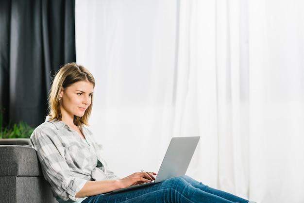 Mujer encantadora que usa la computadora portátil cerca del sofá