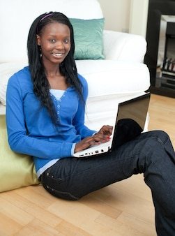 Mujer encantadora que usa una computadora portátil que se sienta en el piso