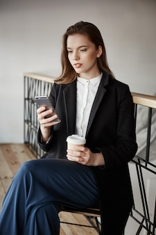 Mujer encantadora en ropa elegante sentado en la cafetería, tomando café mientras sostiene el teléfono inteligente
