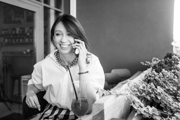 Mujer encantadora sonriente llamando con teléfono celular mientras está sentado solo en la cafetería durante el tiempo libre. imagen en blanco y negro.